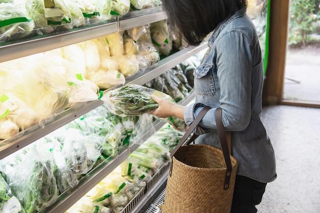 여자는 슈퍼마켓 상점에서 신선한 야채를 쇼핑