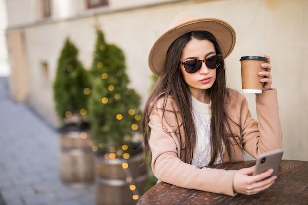 여자는 커피 컵과 전화 캐주얼 옷 어두운 선글라스 카페 드레스 테이블에 앉아있다