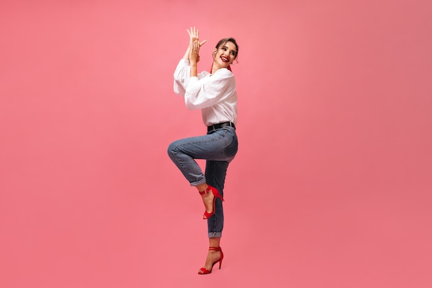 Lady in jeans and white shirt dancing on pink background.  cheerful girl in bright stylish red shoes cute smiling and posing for camera.