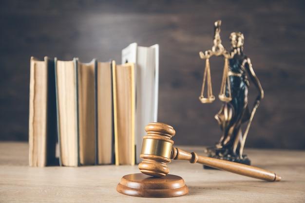 本と机の上の裁判官と正義の女性