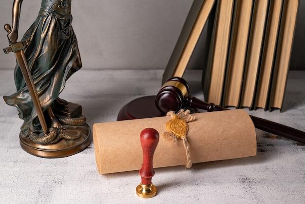 Леди джастис, молоток судьи, книги, пергаментный свиток с печатью и печатью на старом деревянном столе