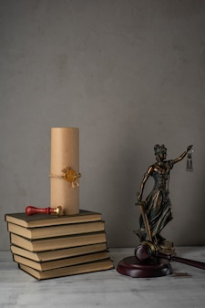 Lady justice, judge's gavel, books, parchment scroll with seal and stamp on an old wooden table