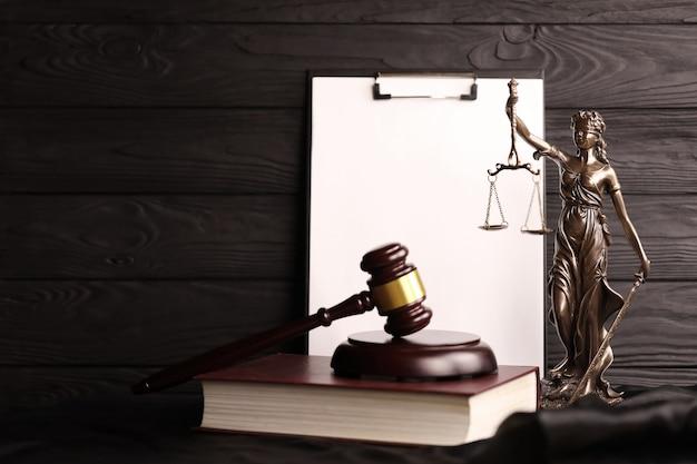 정의의 여신 또는 정의의 로마 여신 justitia. 빈 종이 배경 복사 공간에 판사 망치와 갈색 책에 동상. 사법 재판, 법정 절차 및 변호사 작업의 개념