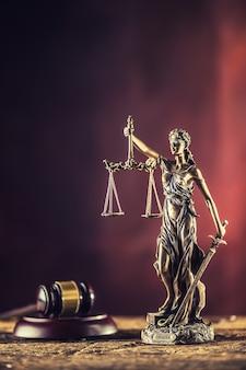 Леди джастисия держит меч и масштабную бронзовую фигурку с молотком судьи на деревянном столе.