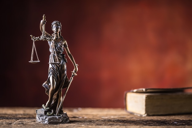 Lady justicia holding sword and scale bronze figurine with book on wooden table.