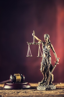 Lady justicia holding sword and scale bronze figurine with judge hammer on wooden table.