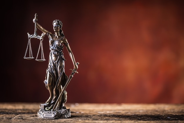 Lady justicia holding sword and scale bronze figurine on wooden table.