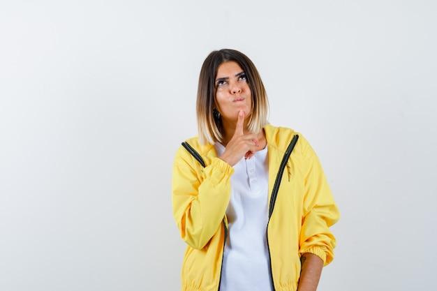 Signora che tiene il dito sul mento in maglietta, giacca e sembra speranzosa, vista frontale.