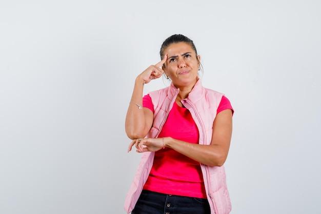 Дама держит палец на висках в футболке, жилете и выглядит задумчиво