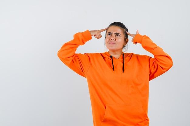 Signora che tiene le dita sulla testa in felpa con cappuccio arancione e sembra pensierosa