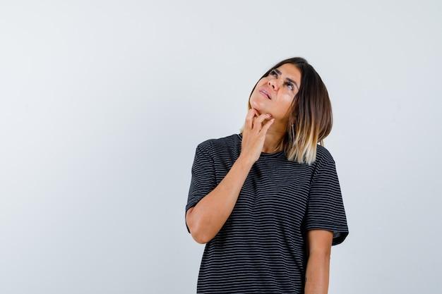 Signora che tiene la mano sotto il mento in maglietta nera e sembra sognante. vista frontale.