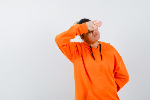 Signora che tiene la mano sulla testa in felpa con cappuccio arancione e sembra triste