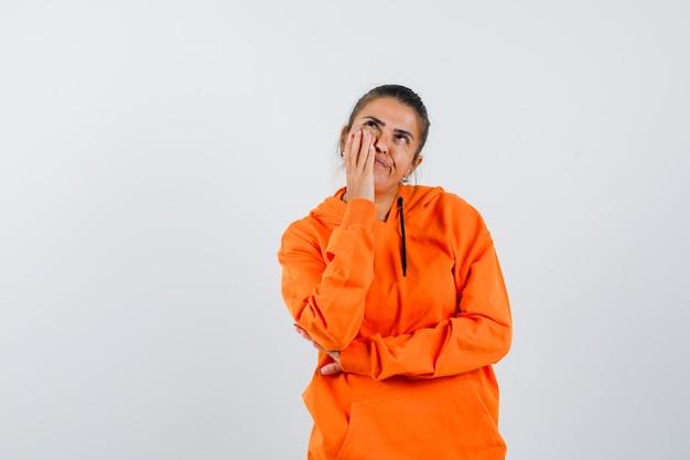 Леди держит руку на щеке в оранжевой толстовке с капюшоном и задумчиво смотрит