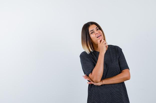 黒のtシャツで顎を握りしめ、誇らしげに見える女性、正面図。