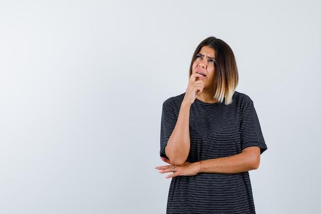 黒のtシャツで顎を握りしめ、思慮深く、正面から見ている女性。
