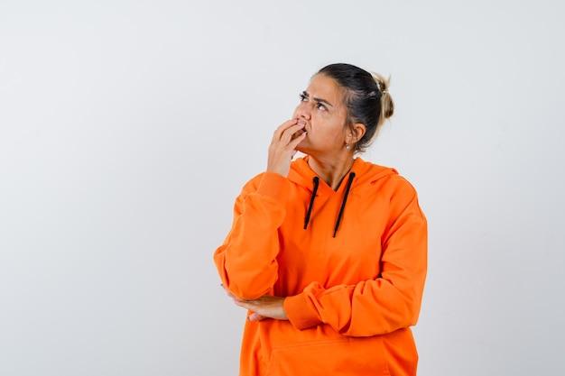 Дама в оранжевой толстовке с капюшоном держит руку на подбородке и выглядит задумчивой