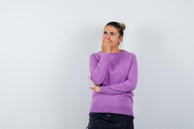 Дама в шерстяной блузке держит руку на подбородке и выглядит мечтательно