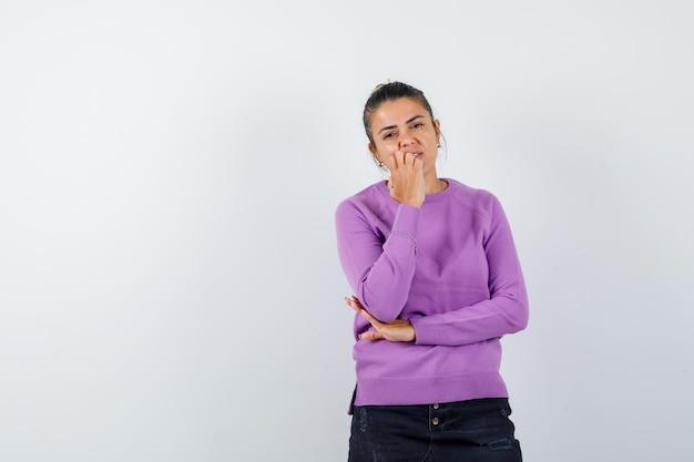 Дама в шерстяной блузке держит руку за подбородок и задумчиво смотрит