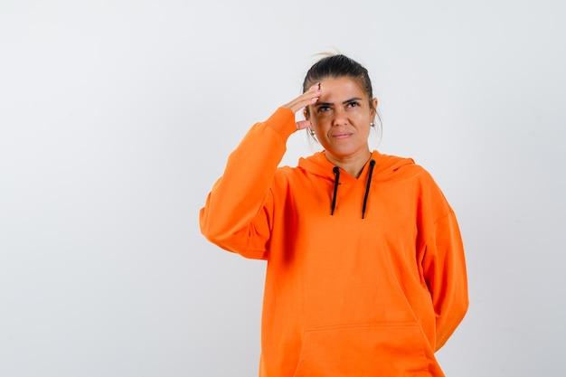 Леди держит руку над головой в оранжевой толстовке с капюшоном и выглядит мечтательно