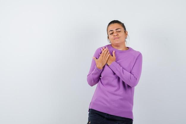 Signora che tiene le mani sul petto in camicetta di lana e sembra calma