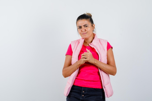 Дама держит руки сцепленными в футболке, жилете и выглядит задумчиво