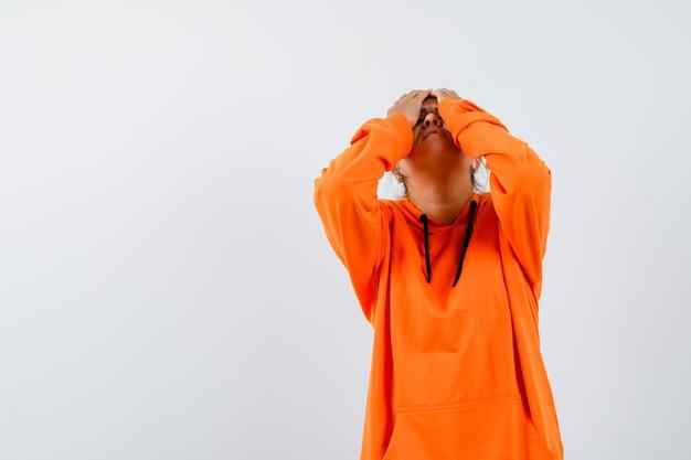 Lady keeping hands on head in orange hoodie and looking wistful