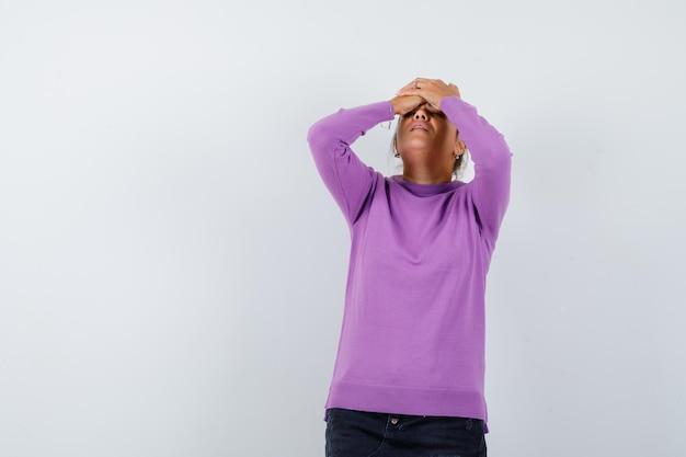 Signora che tiene le mani sulla testa in una camicetta di lana e sembra malinconica
