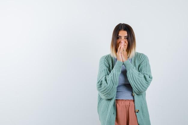 カジュアルな服装で祈りのジェスチャーで手を保ち、希望に満ちた女性。正面図。