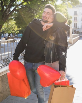 Lady kissing young smiling guy with packets and balloon on street