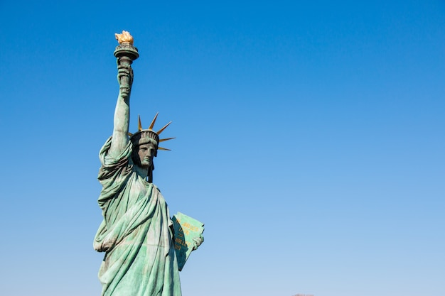 Lady liberty juxtaposed stand against rainbow bridge