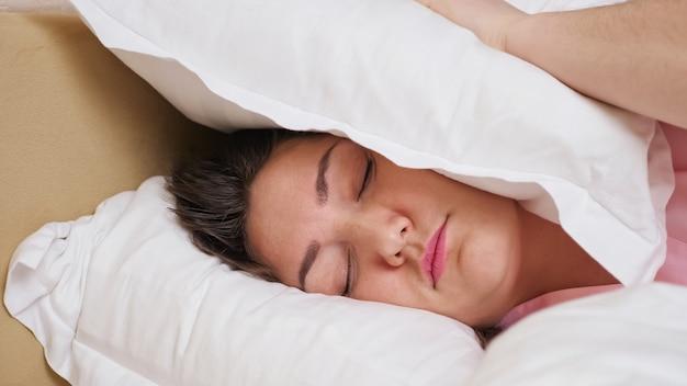 女性は枕で耳を閉じるベッドに横たわっています