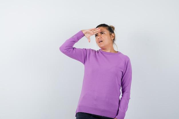Дама смотрит вдаль с рукой над головой в шерстяной блузке и смотрит сосредоточенно