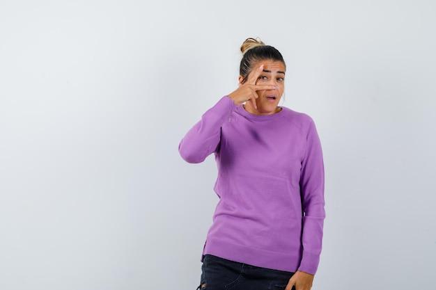 Signora che guarda tra le dita in camicetta di lana e sembra curiosa