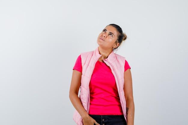 Дама смотрит вверх в футболке, жилете и выглядит задумчиво