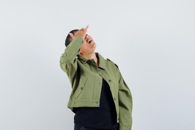 ジャケットの頭の上に手で見上げる女性