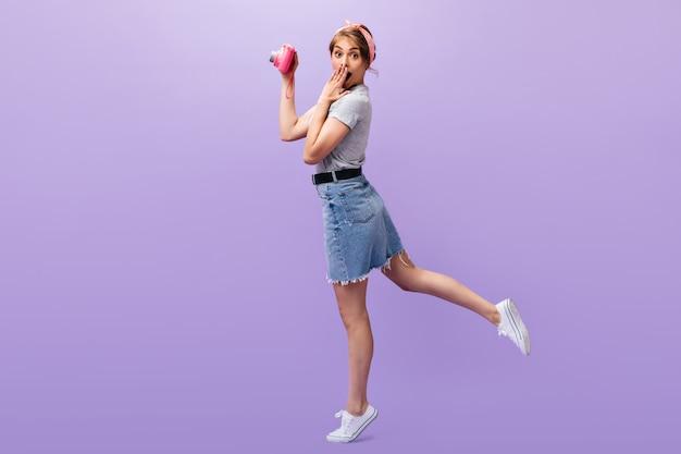 레이디는 충격을 받고 분홍색 카메라를 들고 있습니다. 여름 유행 복장 pose.n 보라색 배경에 놀란 된 멋진 여자.