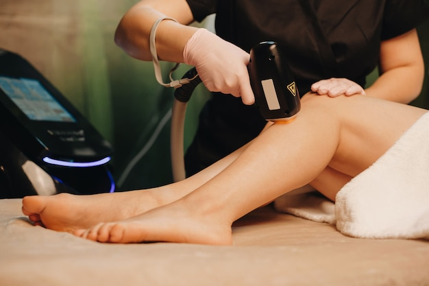 Lady lying on the couch while having an epilation sessions at the spa salon with modern apparatus