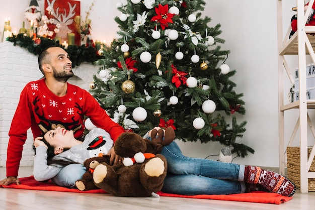 Lady lying on guy near soft toys