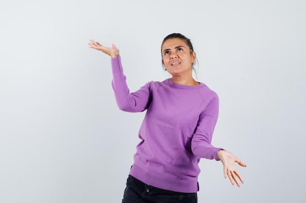 ウールのブラウスで体重計のジェスチャーをし、希望に満ちた女性