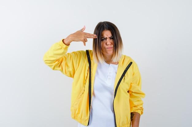 Tシャツ、ジャケットで自殺ジェスチャーをし、意地悪に見える女性。正面図。
