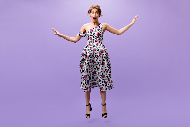 Lady in midi dress jumping on purple background. wonderful young woman in colorful stylish clothes posing on isolated backdrop.