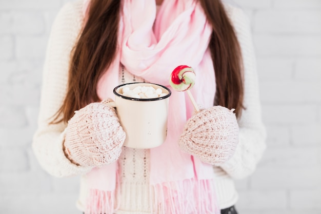 Lady in mittens and scarf holding cup with marshmallows and lollipop