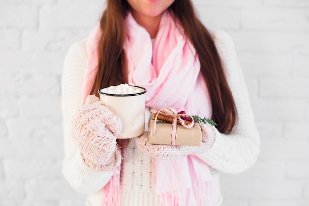 Lady in mittens and scarf holding cup with marshmallows and present box