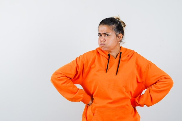 Lady in orange hoodie holding hands on waist and looking spiteful