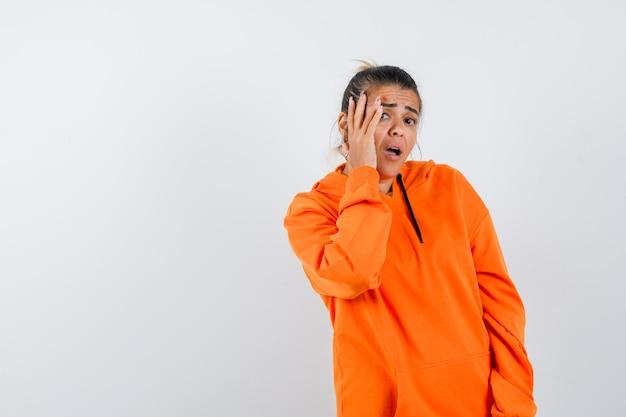Lady in orange hoodie keeping hand on cheek and looking scared