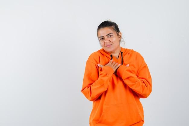 Signora in felpa con cappuccio arancione che tiene le mani sul petto e sembra allegra