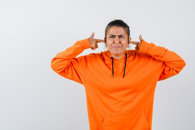 Lady in orange hoodie plugging ears with fingers and looking irritated