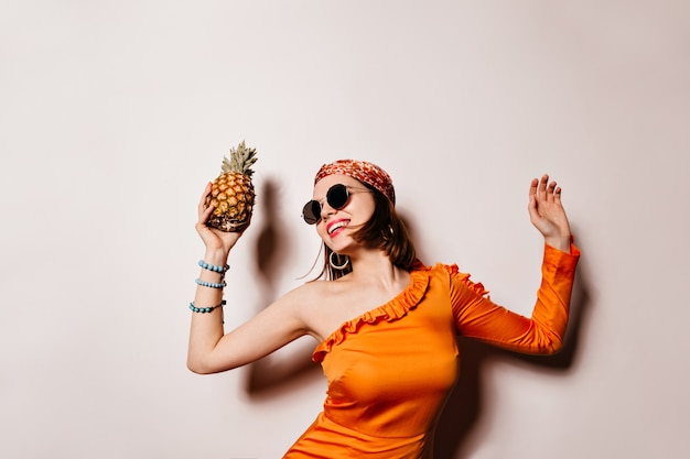 Lady in orange outfit laughs, dances and holds pineapple on white space.