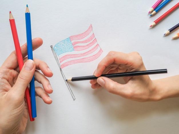 アメリカ合衆国の国旗を描いている女性。