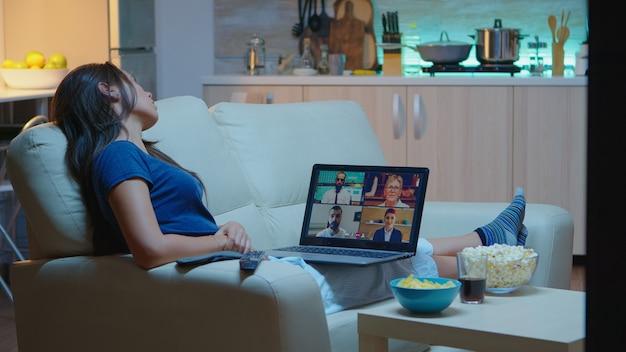 Signora in pigiama seduta sul divano durante un incontro online con i partner del progetto. lavoratore remoto che discute in videoconferenza consultando i colleghi utilizzando videochiamate e webcam che lavorano al laptop
